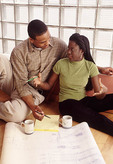 Young black couple looking at architects plan or drawings for new home.