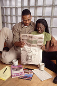 Young black couple searching for a new home or apartment in newspaper.