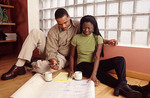 Young black couple look at architect's  drawings for a new home