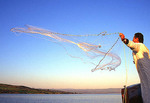 Fisherman, dressed as Saint Peter, casts a net on the Sea of Galilee, Israel.