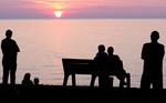 People silhouetted watching the sunset on lake Erie.