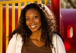 Portrait of a smiling black african american woman in front of colorful equipment in a park.