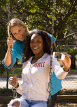 Two young women on a swing laughing and having fun, taking pictures on an IPhone.