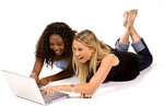 Two young women searching the Internet and laughing.