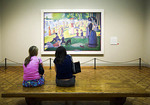 Two women viewing a painting by Georges Pierre Seurat at The Art Institute of Chicago.