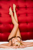 Woman with long legs on red satin bed.