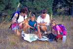 Young family hiking and navigating using map and compass