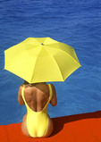 Woman at pool side with yellow umbrella.