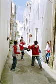 Kids playing soccer in the streets of Italy.