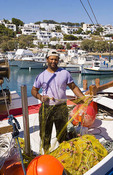 Fisherman repairing nets in a harbor with fishing ships in the background in the little village of Pisso Livadi, Greece.