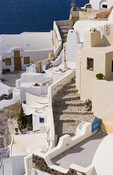 Beautiful village of Oia with white old buildings looking down at Santorini, Greece.