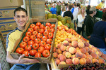 A smiling vendor showing off his tomatoes for sale at the Westside Market in Cleveland, Ohio.