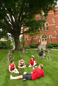 Family relaxing on a lawn in front of a gothic building after a bike ride.
