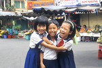 Three asian kids hug each other and laugh.