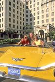 Three friends in a fancy yellow car.