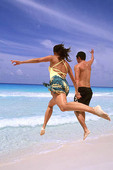 Fun couple running and jumping in Cancun on beaches of Mexico.