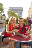 Tourist couple at café on Famous Champs Elysees and Arc de Triomphe in Paris France
