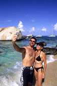 Beautiful rock formation rocks with couple and cell camera phone at The Baths of Virgin Gorda in British Virgin Islands