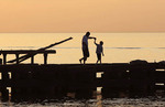 Silhouetted Father and son walk out on old pier over Lake Erie