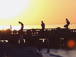 Kids play on old pier at sunset with Lake Erie in background