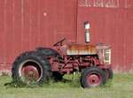Old farm tractor next to red barn