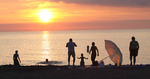 Family silhouetted at sunset on the beach in the Summer time