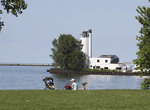 Couple enjoy view of Lake Erie from Wendy Park in Cleveland with old Coast Guard Station in background