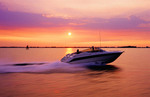 Couples running motor boat with wake and excitement as it moves thru water with speed at sunset