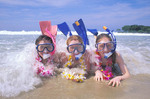 Young girls with snorkel gear wearing leis play in ocean surf Hawaii