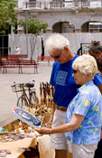 Tourist couple buying artwork from stand in town square in Santa Clara Cuba