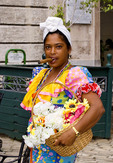 Colorful woman in costume with flowers and cigar in Old Havana Habana in Cuba