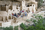 A group of tourists accompanied by a National Park Service guide tour the Cliff Palace ruins, Mesa Verde National Park