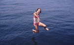 Young girl jumping in the Ocean