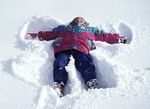 Young girl makes a snow angel in fresh snow