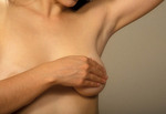 Woman giving her self a breast exam