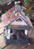 Kitten sleeping in a birdhouse