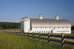 Late afternoon sun on the fence and white barn at D H Day Farm, Leelanau County; Michigan