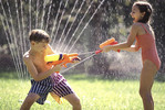 Young kids having a squirt gun fight