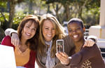Mixed ethnic women friends relaxing at home laughing with cell phone camera I Phone