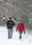 Young couple walking with dog in the snow