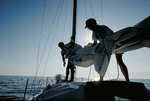 Man and woman bringing in sails on a sailboat