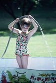Young girl filling small pool with garden hose