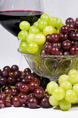 A glass of red wine stands behind bunches of red and green grapes with a white background.