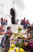 Woman in colorful print fabrics selling colorful flowers on steps of old Cathedral in Chichicastenango Guatemala in the markets on market day