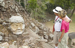 Tourist couple looking at old mask ruins at famous Mayan temples of Copan Honduras in Central America