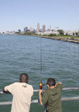 Young boys fishing off pier on Lake Erie with Cleveland in background