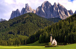 Beautiful isolated lonely church called Rainui in valley  in the Italian Dolomites village of Val Di Funes mountains Alpine area  of Italy with Dolomites looming behind