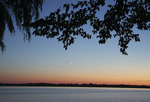 Sliver moon over lake at sunset