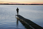 Woman at end of dock watching the sunset
