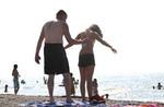 Sunbathers spraying on sun black protection